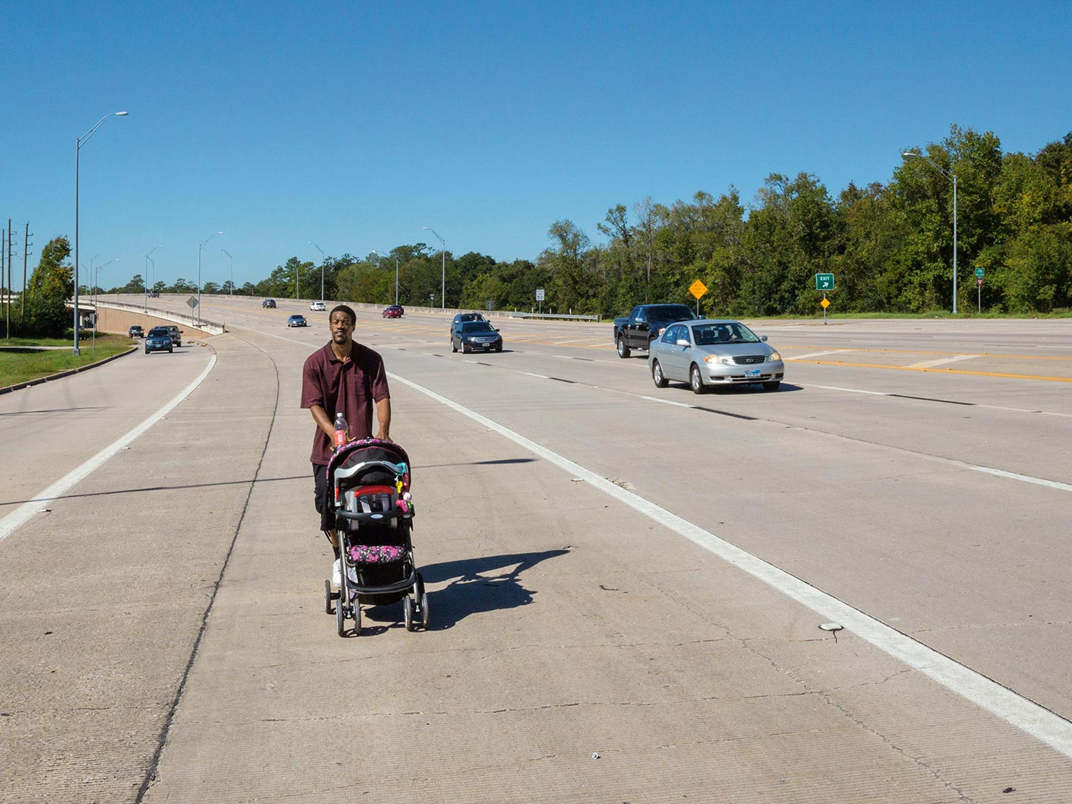 photo of a young father walking along a highway near houston