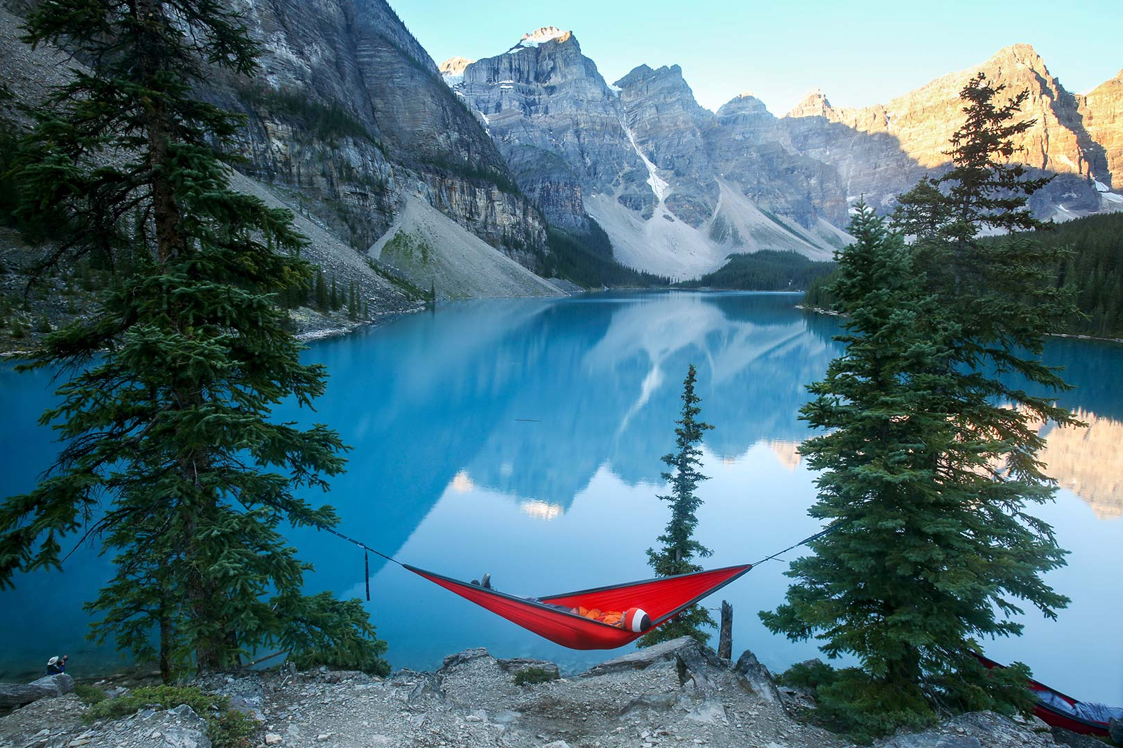 Picture of a visitor resting in a hammock near Moraine Lake, Banff National Park, Canada
