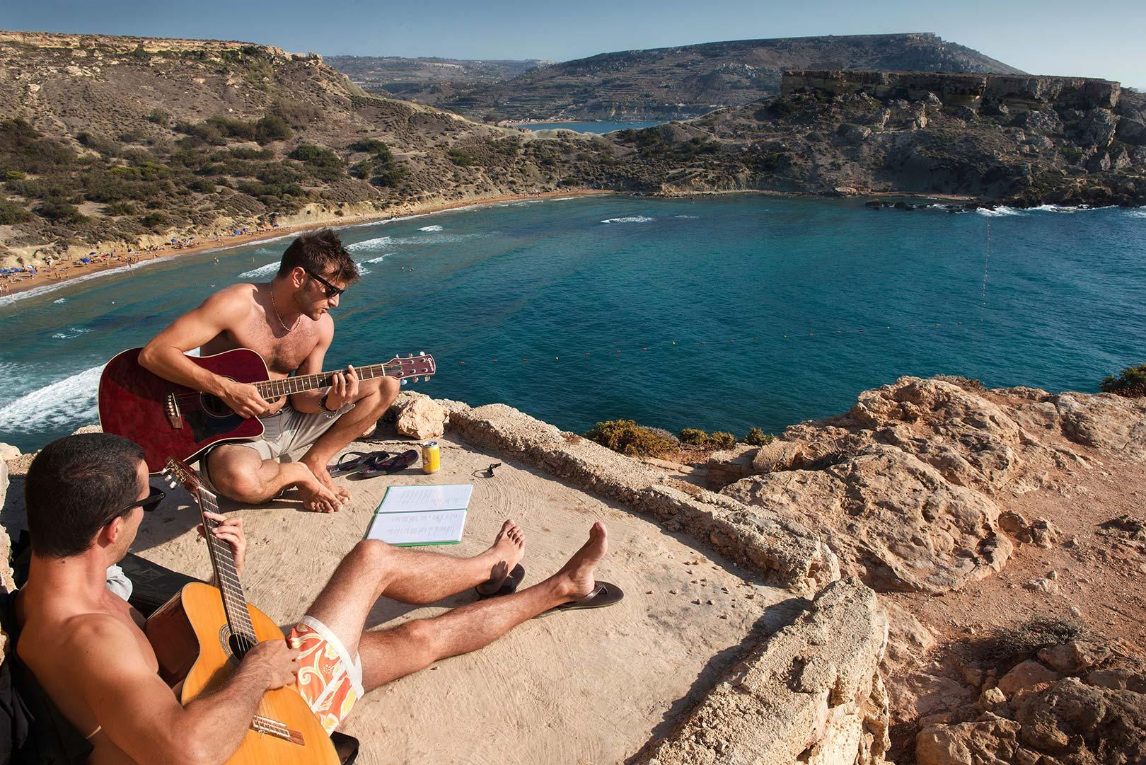 Picture Of Young Men Playing Guitar Above The Għajn Tuffieħa Beach Malta