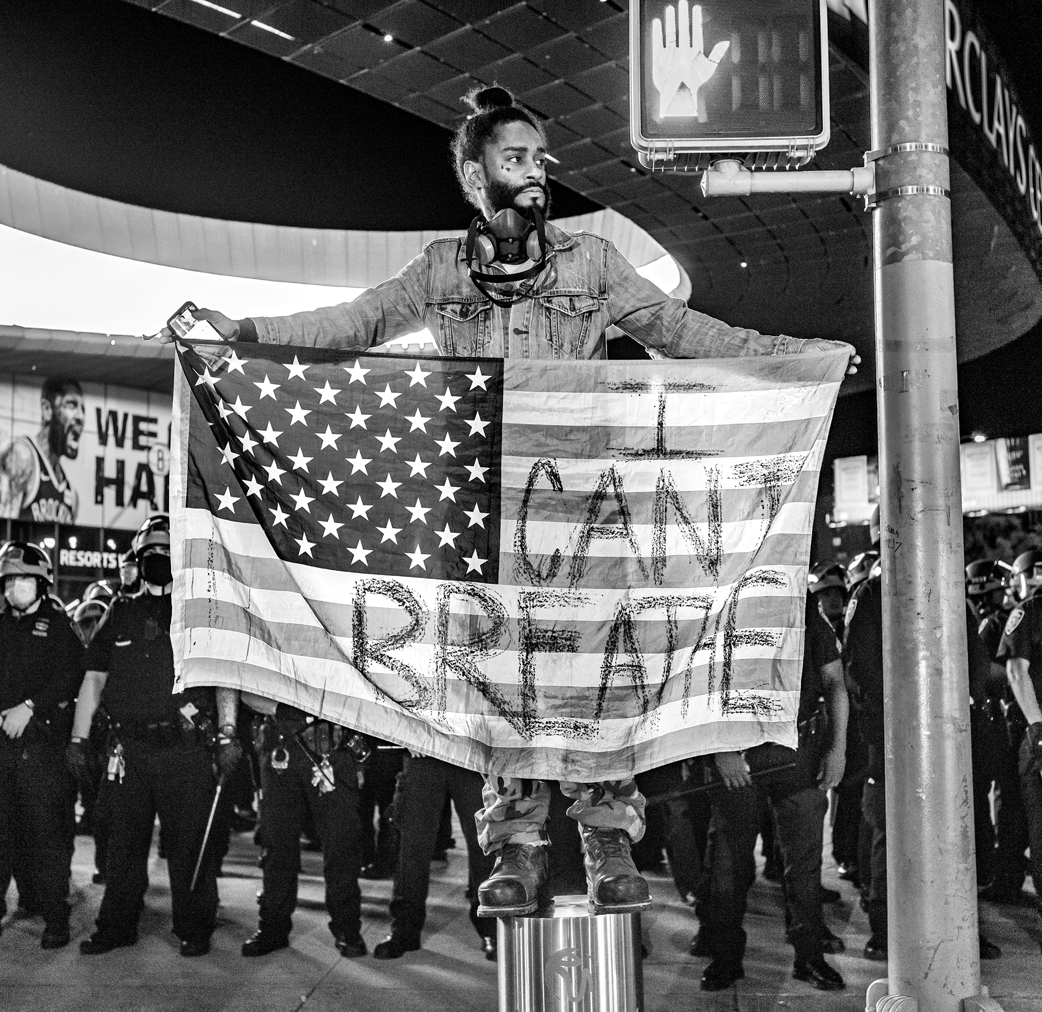 """Picture of a person standing on a street divider holding an American flag that reads """"I can't breathe"""""""