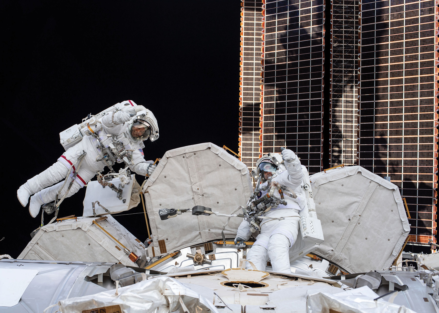 Picture of two astronauts floating alongside a space station