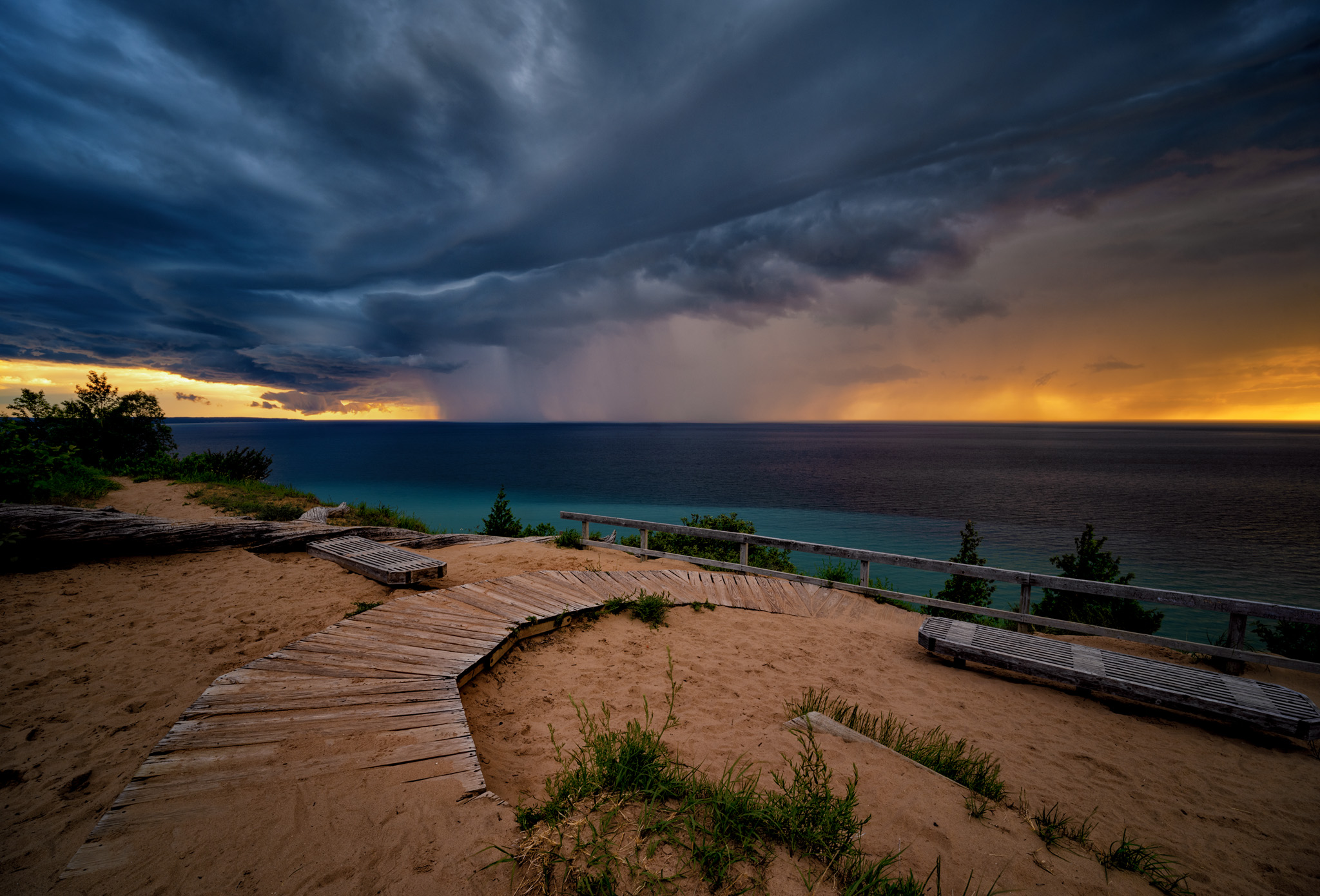 Picture of a boardwalk over sand by Lake Michigan under stormy skies