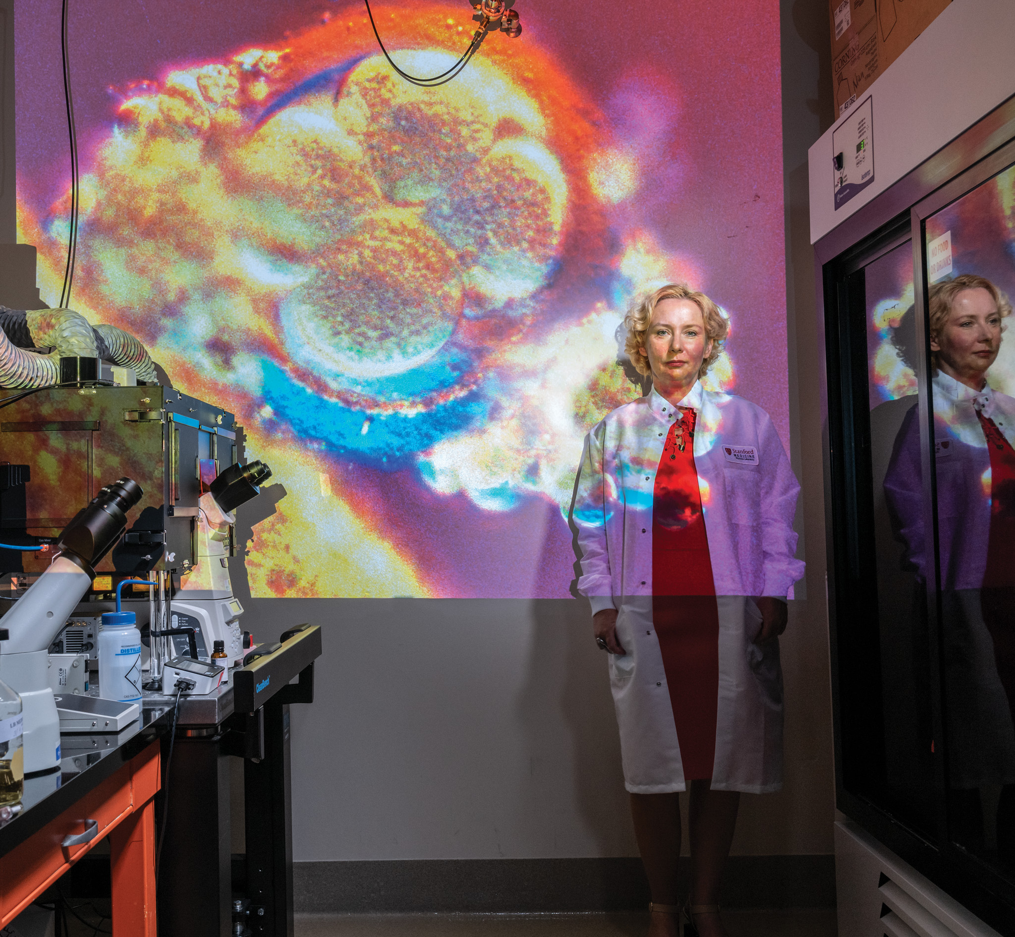 Picture of a scientist standing against a wall with a projection of cells on it