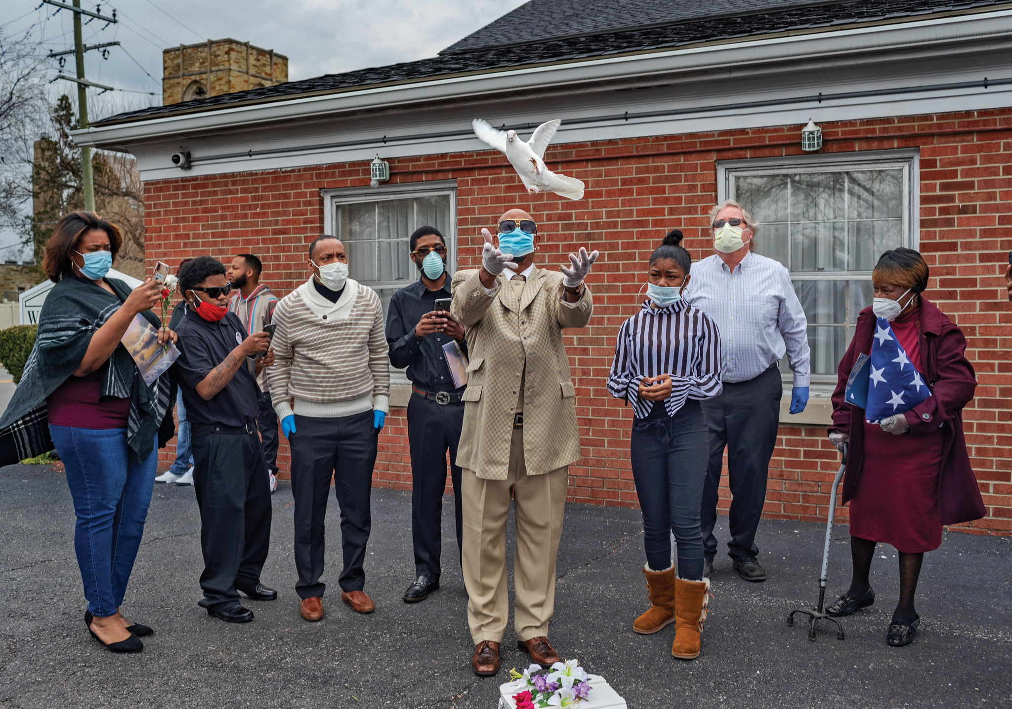 Picture of funeral attendees watching as a man releases a dove