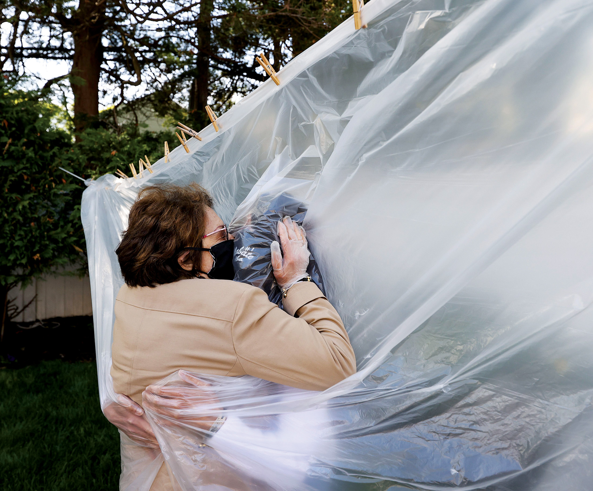 Picture of a woman kissing another person through a plastic sheet