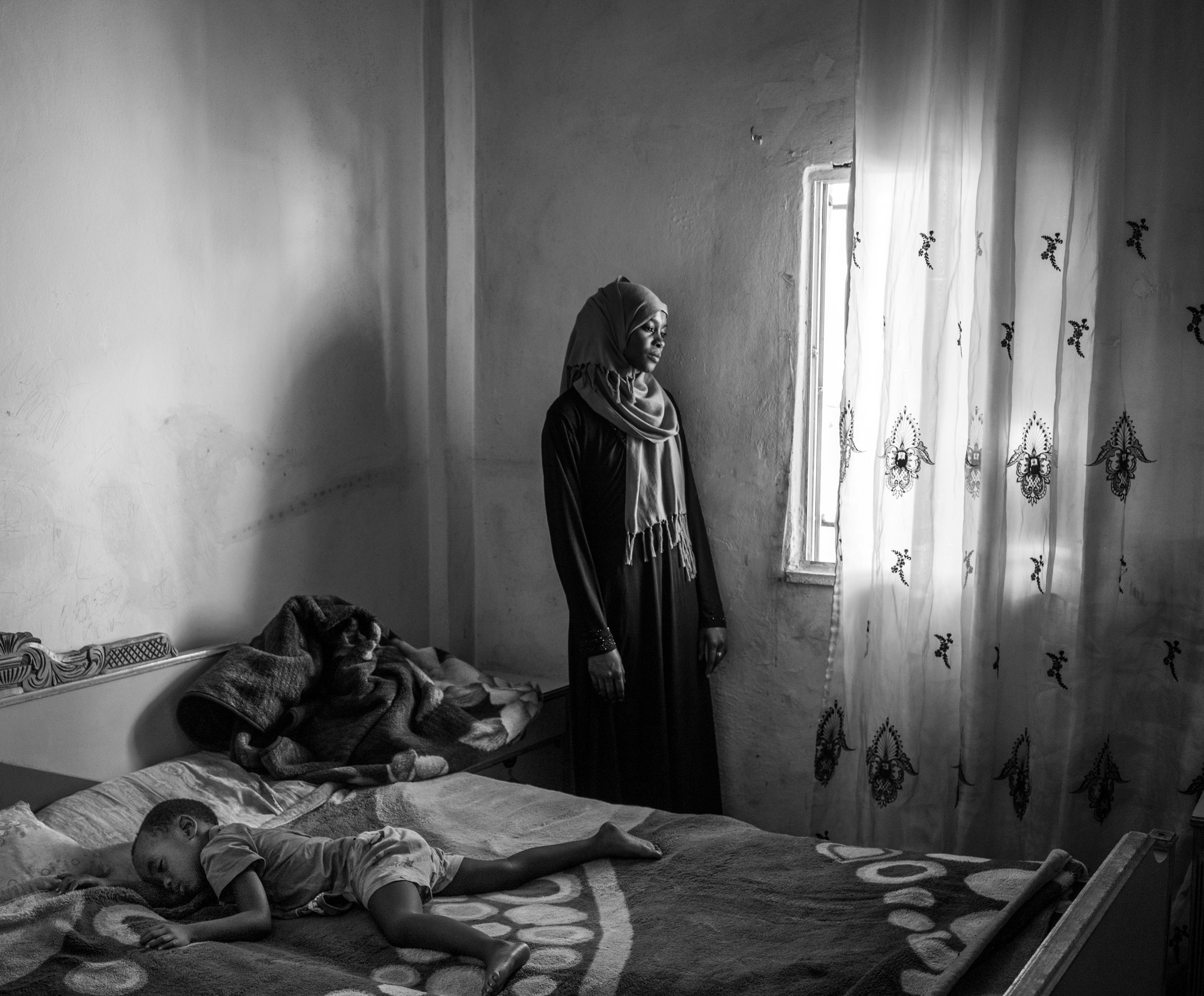 Picture of a mother looking out a window as her child sleeps on a bed
