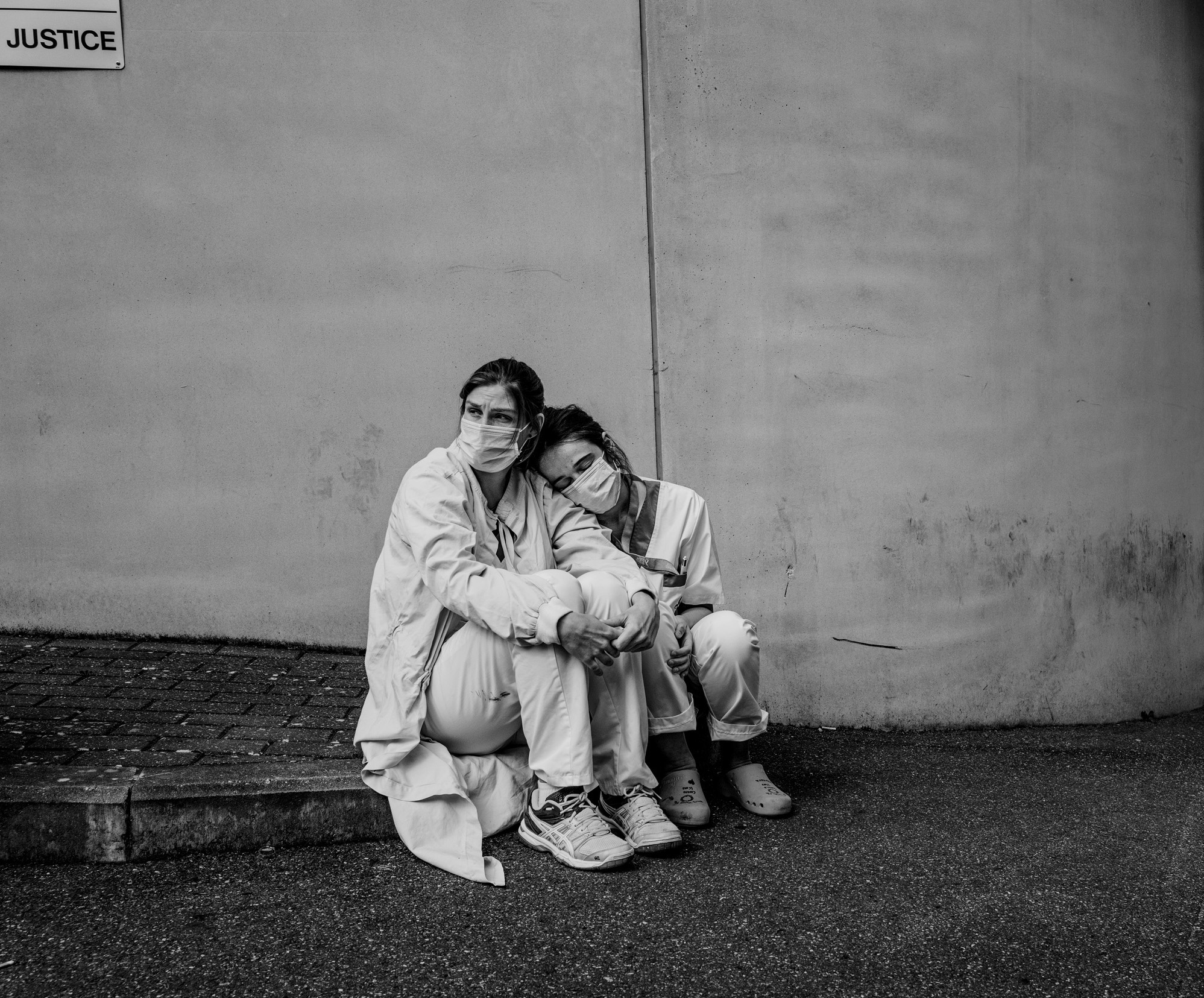 Picture of two nurses sitting on a curb, one tenderly resting her head on the other