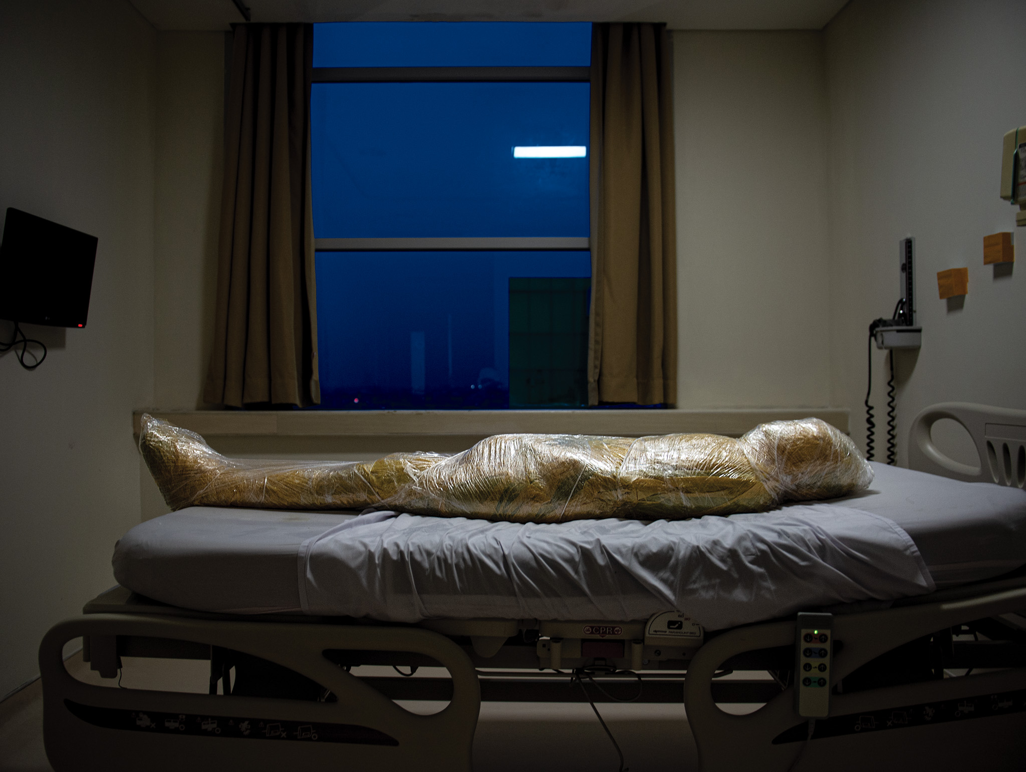 Picture of a human body wrapped in plastic on a hospital bed