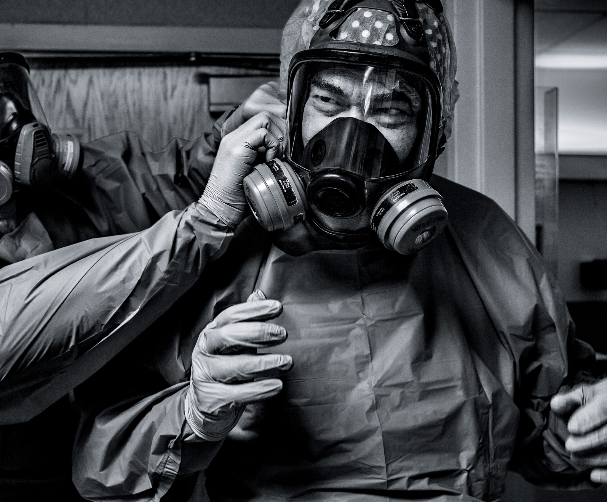 Picture of a doctor strapping a respirator on another doctor's face
