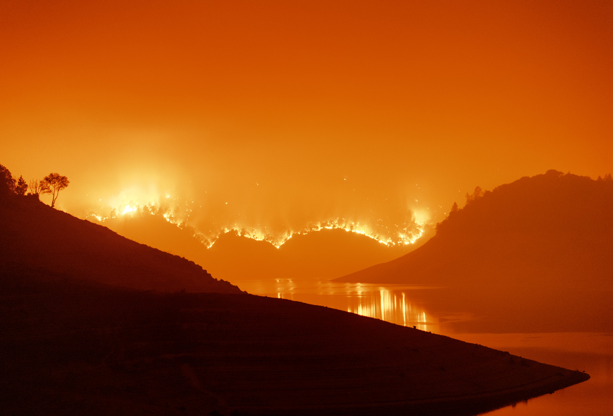 Picture of fires burning down a hillside, causing the landscape to turn a deep orange