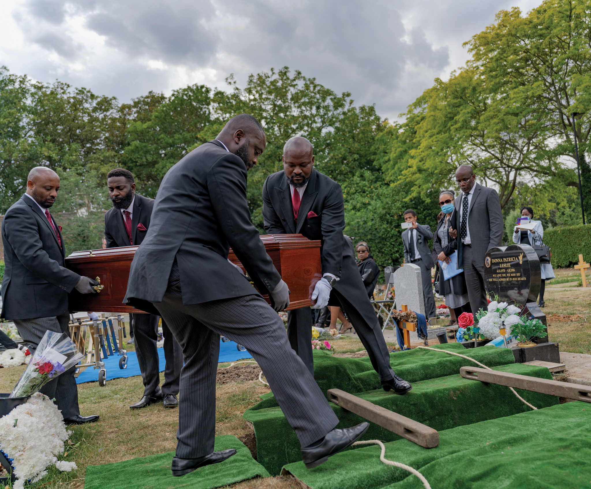 Picture of pallbearers lowering a coffin into a grave