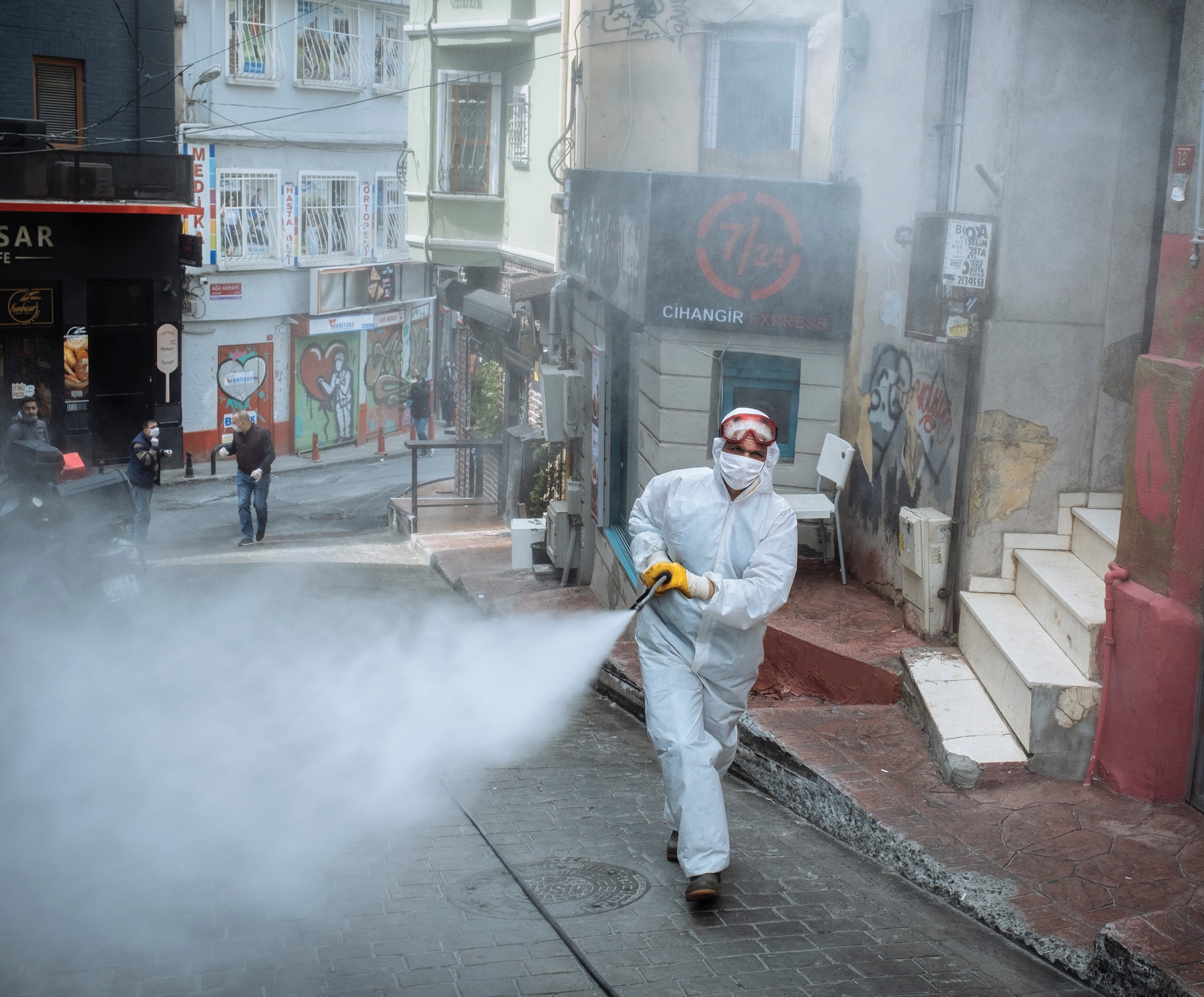 Picture of a person spraying disinfectant on the streets