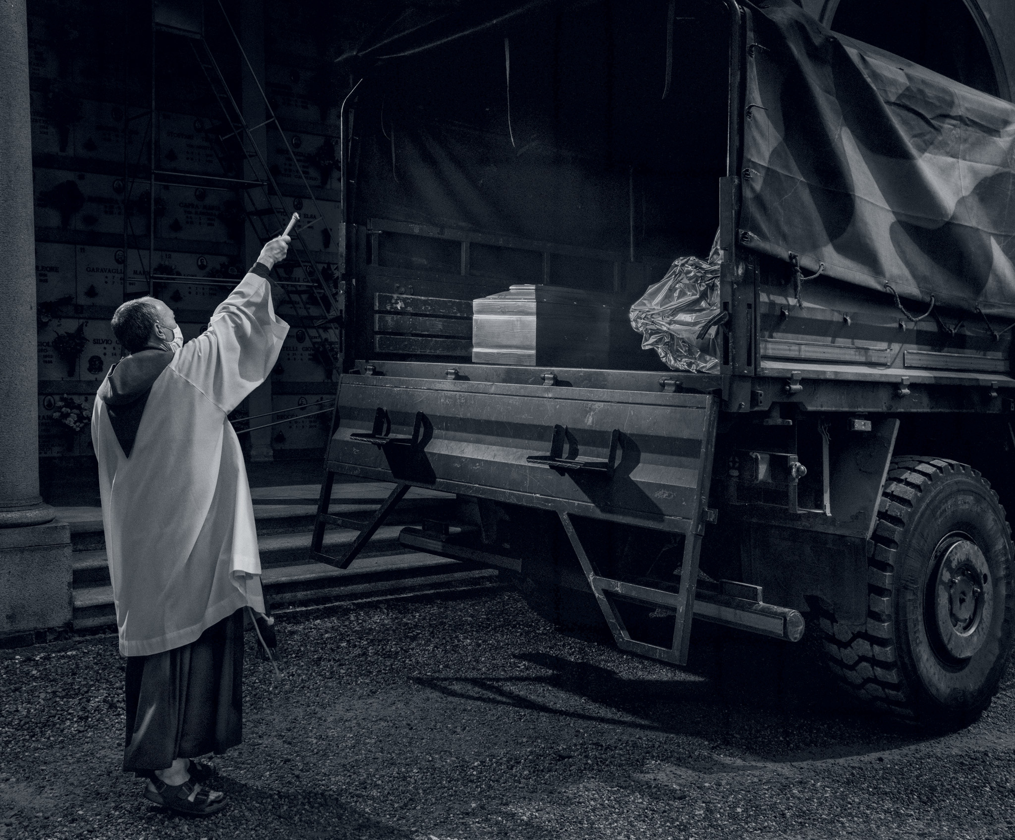 Picture of a priest blessing a truck driving away with a coffin